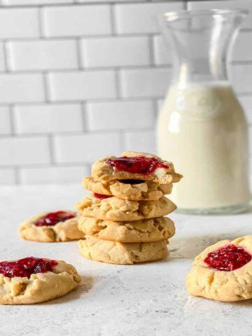 milk jug behind raspberry jam filled shortbread cookies stacked