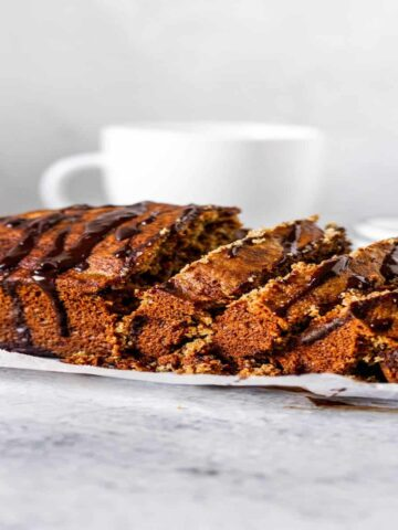 banana bread loaf drizzled with melted chocolate on an antique cooling rack
