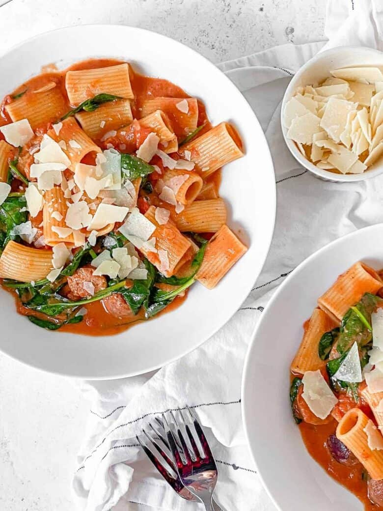 two bowls of rigatoni in a creamy tomato sauce with chicken sausage and spinach with a small bowl of shaved parmesan cheese