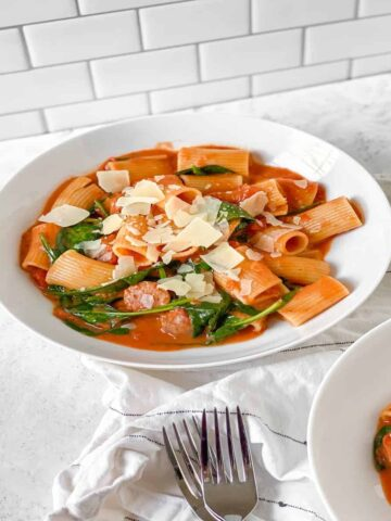 a bowl of rigatoni in a creamy tomato sauce with chicken sausage and spinach