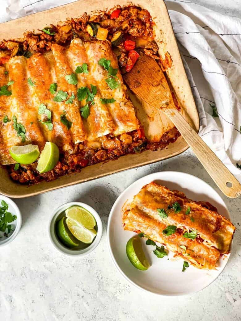 two enchiladas on a plate next to a casserole dish filled with the enchiladas topped with cheese and a ramekin full of lime wedges