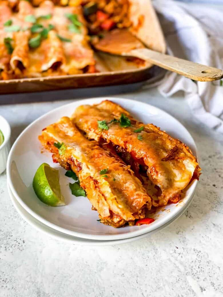 two turkey and vegetable filled enchiladas on a white plate garnished with a lime wedge
