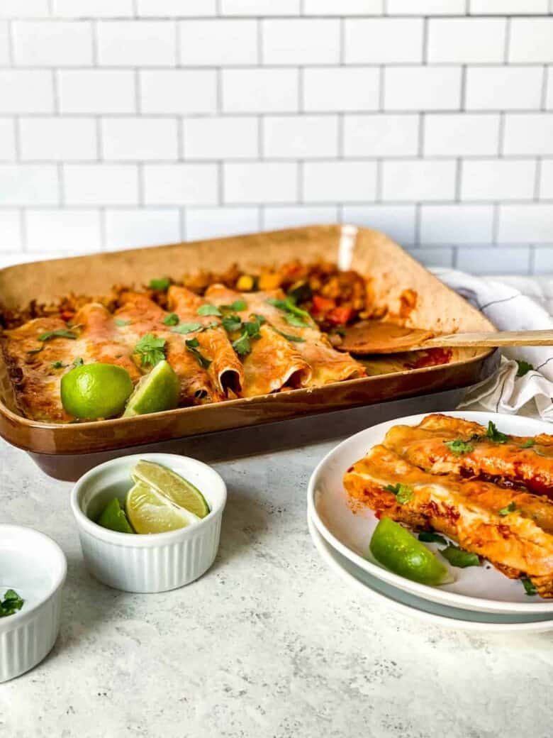 two enchiladas on a plate next to a casserole dish filled with enchiladas topped with cheese and a ramekin full of lime wedges