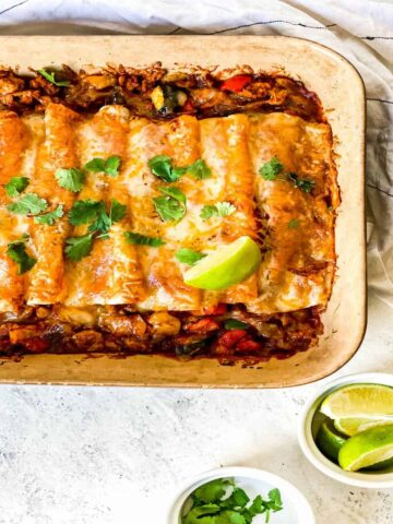 a casserole dish filled with enchiladas topped with cheese and a ramekin full of lime wedges