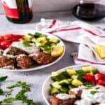 Greek turkey meatballs on white plates with diced cucumber and tomato and scoop of tzatziki sauce in front of a glass and bottle of red wine