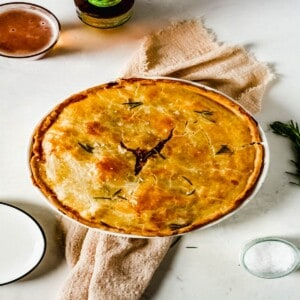 steak and onion pie in a white pie dish on a white background