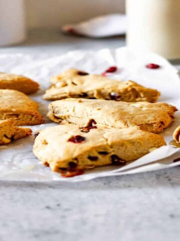 honey dipper in front of white chocolate and cranberry scones on crinkled wax paper