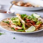 a grilled chicken taco topped with guacamole on a plate