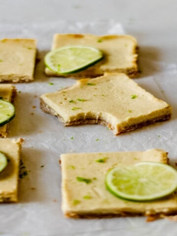 6 key lime pie bars on a piece of wax paper with a bite taken out of one