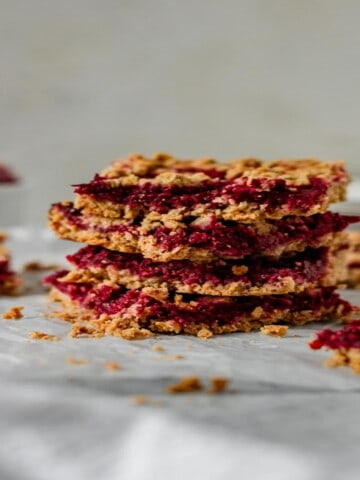four oatmeal bars filled with raspberry stacked