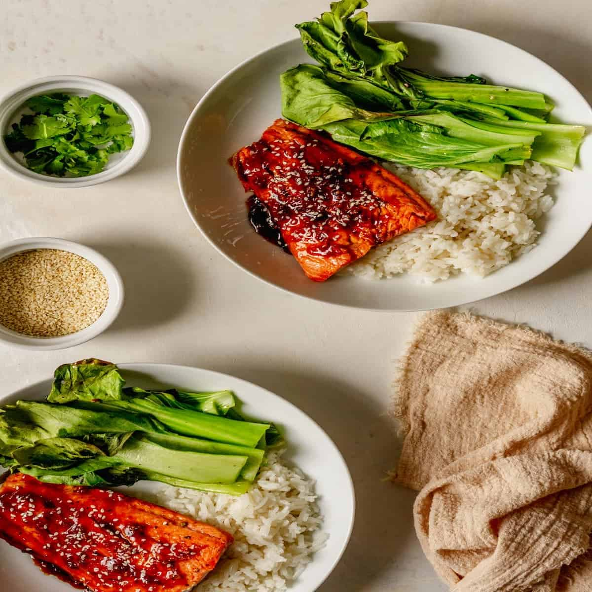 2 plates filled with white rice, baby bok choy and teriyaki salmon