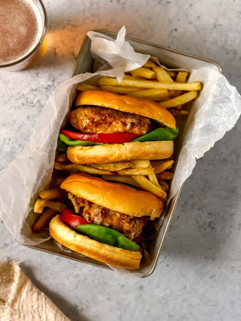 two turkey burgers in a basket with fries