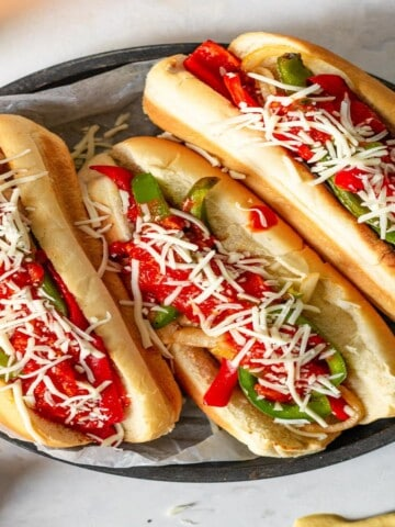 three sausage and peppers sandwiches topped with marinara and cheese