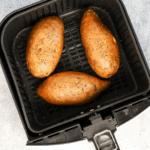 three sweet potatoes in an air fryer basket