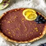 lemon blueberry tart topped with lemon slices and blueberries