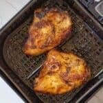 chicken breasts in an air fryer basket