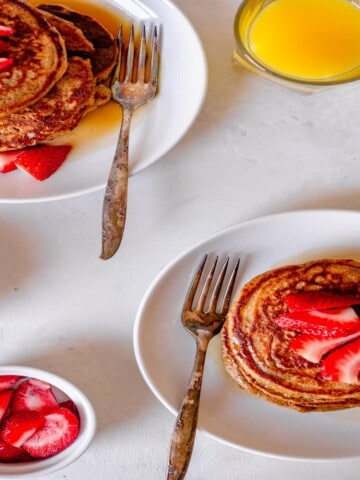 two white plates filled with pancakes and topped with sliced strawberries