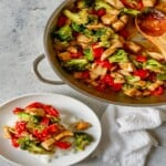 chicken and vegetable stir fry on a plate next to the pan