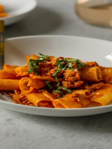 a white bowl filled with rigatoni in a spicy red sauce