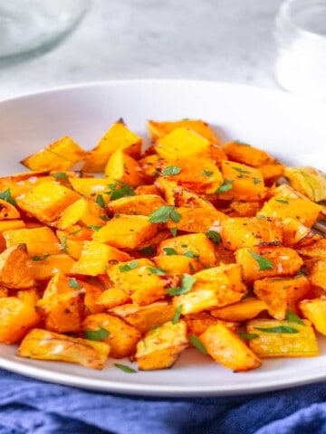 cut butternut squash in a white bowl topped with parsley
