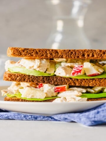 chicken salad with apples in between 3 slices of bread on a white plate