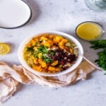 white bowl filled with butternut squash and cranberry quinoa salad ingredients